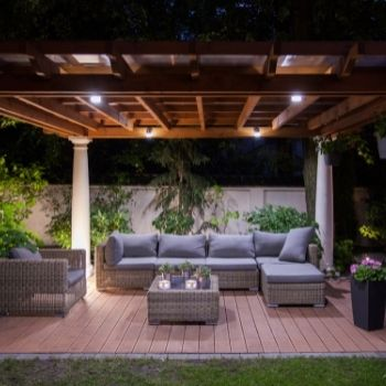 A cozy patio with a timber pergolas decorated with a sofa and table   Landscaping Melton